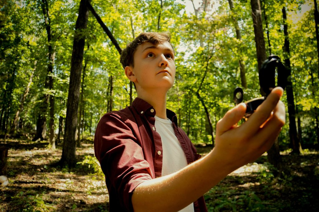 Adolescent finding his way in the woods with a compass